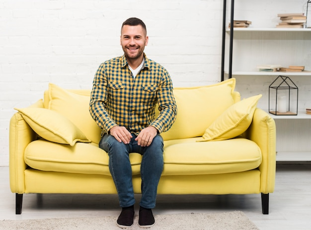 Vista frontal do homem sentado no sofá