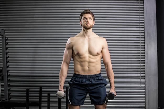 Vista frontal do homem sério, levantamento de peso no ginásio
