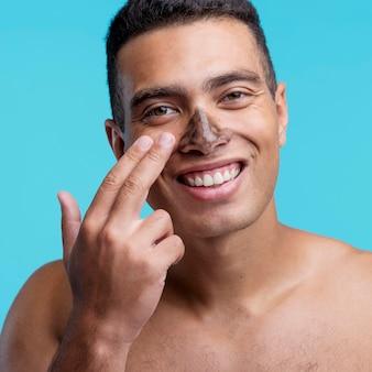 Vista frontal do homem sorridente aplicando máscara no nariz