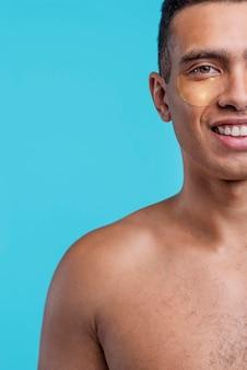 Vista frontal do homem sorridente com tapa-olhos e espaço de cópia
