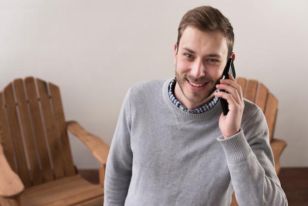 Vista frontal do homem sorridente, falando nos telefones