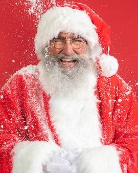 Vista frontal do homem sorridente fantasiado de papai noel com neve