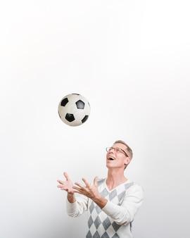 Vista frontal do homem sorridente, jogando com uma bola de futebol