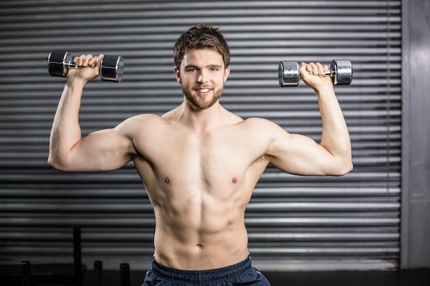 Vista frontal do homem sorridente, levantamento de peso no ginásio crossfit