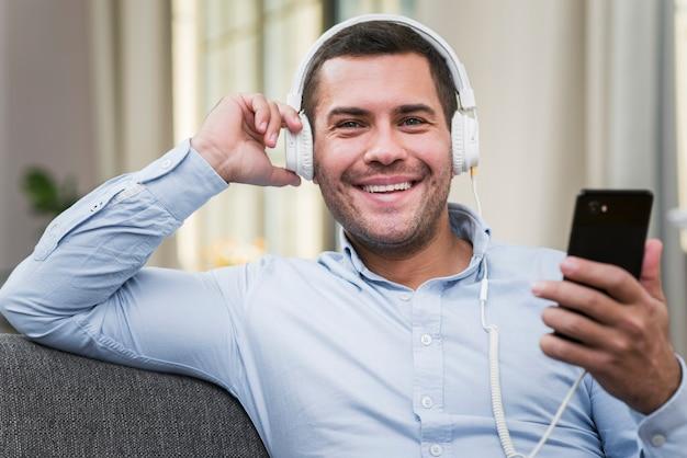 Vista frontal do homem sorridente, ouvindo música