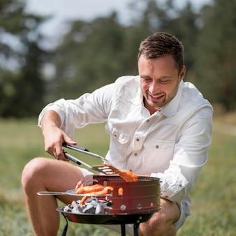 Vista frontal do homem sorridente participando de um churrasco ao ar livre