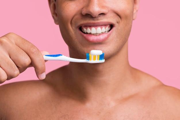 Vista frontal do homem sorridente segurando a escova de dentes com pasta de dente