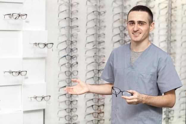 Vista frontal do homem sorridente segurando o par de óculos na mão