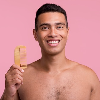 Vista frontal do homem sorridente segurando o pente