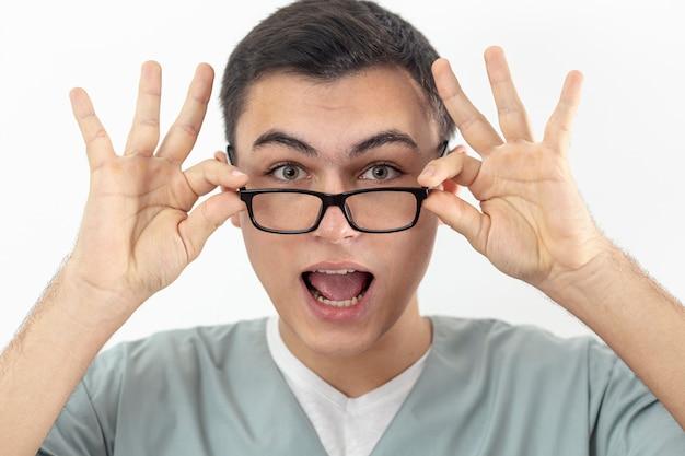 Vista frontal do homem sorridente segurando seus óculos no rosto