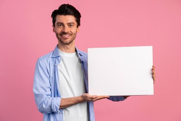 Vista frontal do homem sorridente segurando um cartaz em branco