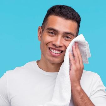 Vista frontal do homem sorridente usando uma toalha no rosto