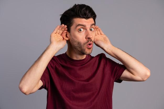 Vista frontal do homem tentando ouvir a conversa