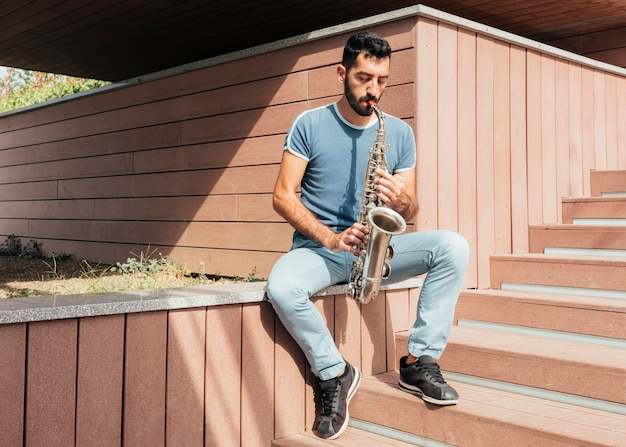 Vista frontal do homem tocando o conceito de saxofone