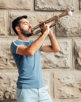 Vista frontal do homem tocando trompete