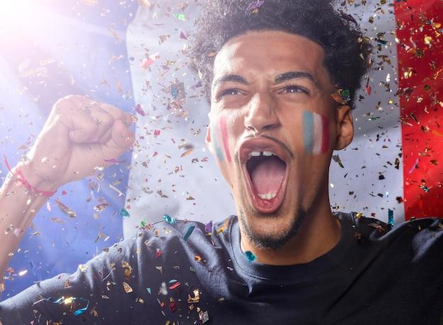 Vista frontal do homem torcendo com a bandeira francesa e confetes