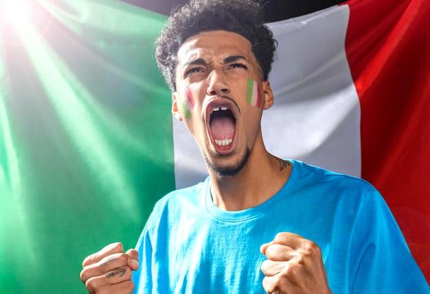 Vista frontal do homem torcendo com a bandeira italiana