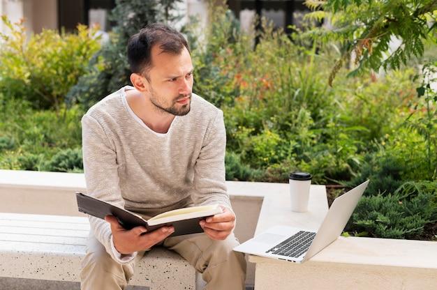 Vista frontal do homem trabalhando ao ar livre com laptop e livro