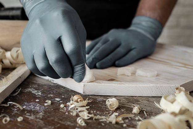 Vista frontal do homem trabalhando em close-up de madeira