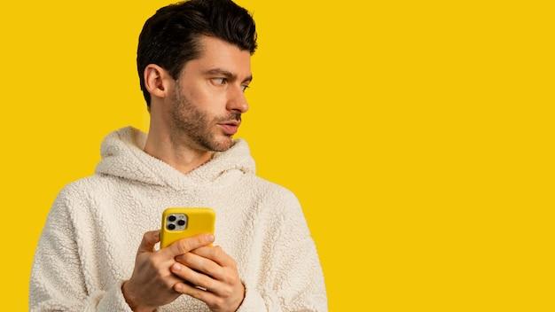 Vista frontal do homem usando smartphone com espaço de cópia