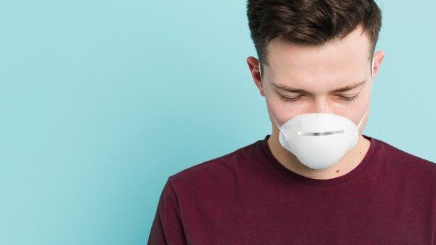 Vista frontal do homem vestindo máscara médica e posando com os olhos fechados