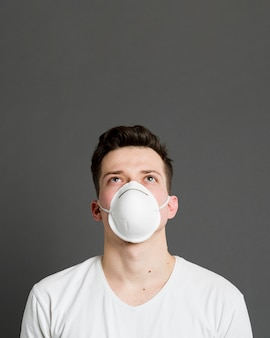 Vista frontal do homem vestindo uma máscara médica com espaço de cópia