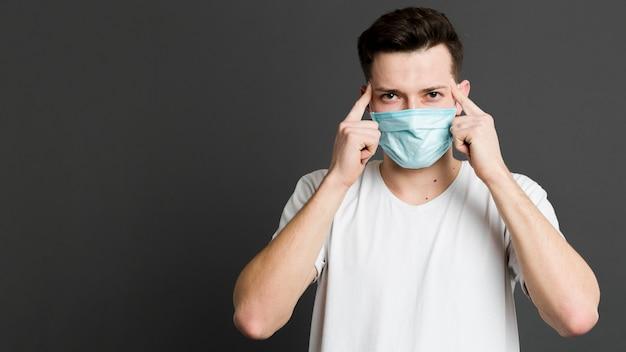 Vista frontal do homem vestindo uma máscara médica e apontando para seus templos