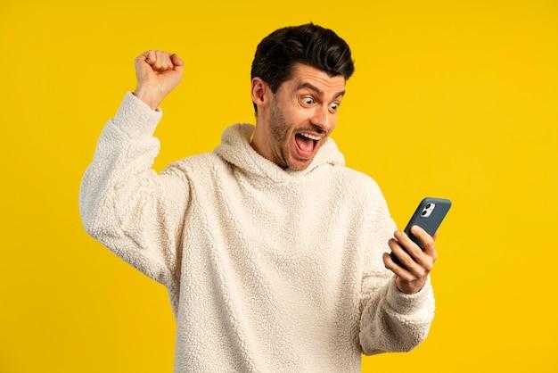Vista frontal do homem vitorioso segurando um smartphone
