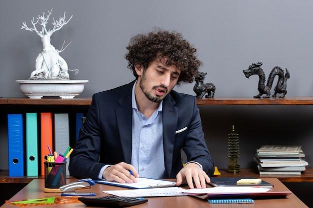 Vista frontal do incansável jovem empresário trabalhando no escritório