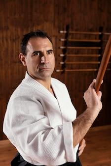 Vista frontal do instrutor de artes marciais na sala de prática com uma vara de madeira