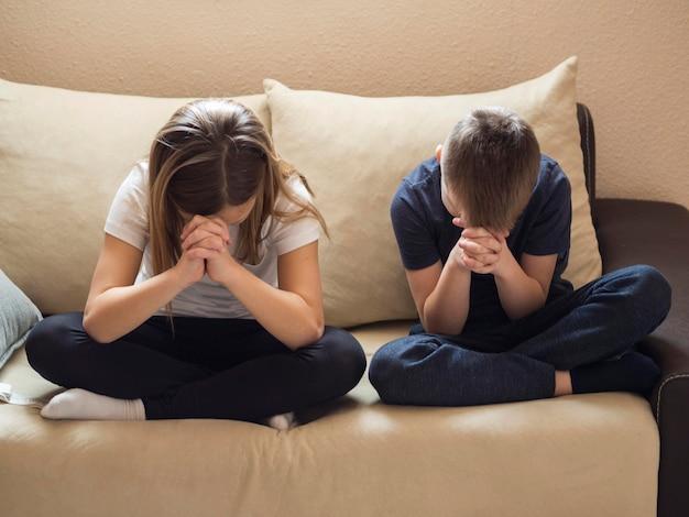 Vista frontal do irmão e irmã rezando