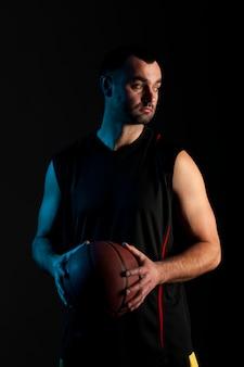 Vista frontal do jogador de basquete estóico segurando uma bola