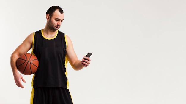 Vista frontal do jogador de basquete, posando com espaço smartphone e cópia