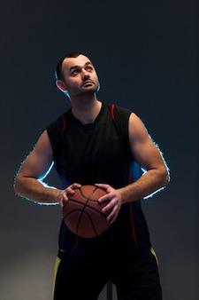 Vista frontal do jogador de basquete, segurando uma bola com as duas mãos Foto gratuita
