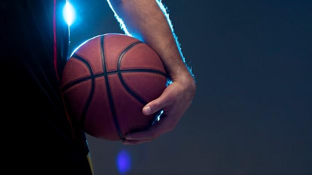 Vista frontal do jogador de basquete, segurando uma bola com espaço de cópia
