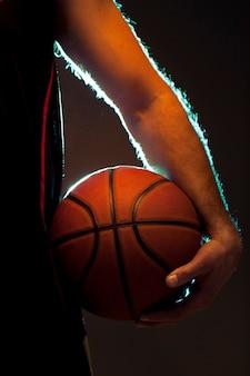 Vista frontal do jogador de basquete, segurando uma bola
