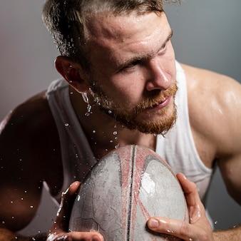 Vista frontal do jogador de rúgbi molhado segurando uma bola