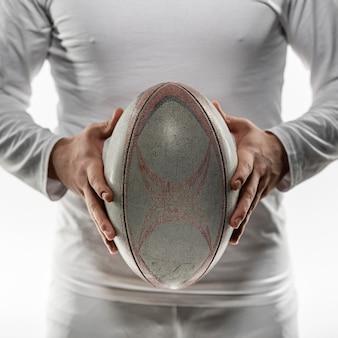 Vista frontal do jogador de rúgbi segurando a bola com as duas mãos