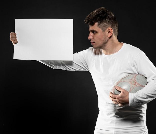 Vista frontal do jogador de rúgbi segurando uma bola e um cartaz em branco