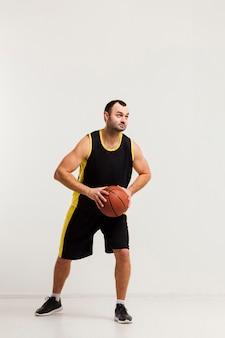 Vista frontal do jogador masculino prestes a saltar com basquete nas mãos