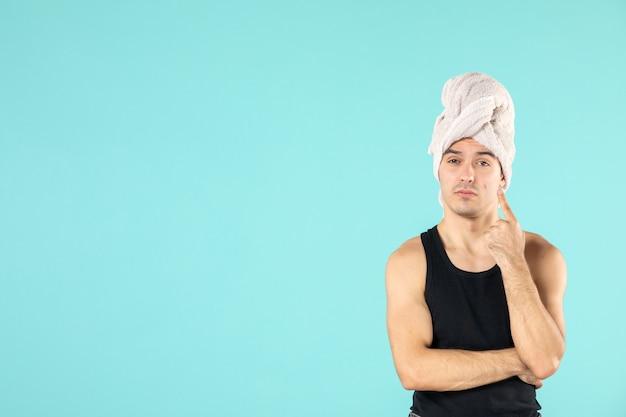 Vista frontal do jovem após o banho na parede azul