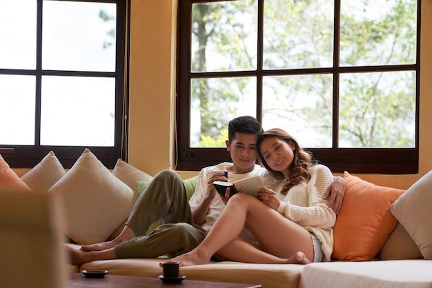 Vista frontal do jovem casal carinhos no sofá com um livro