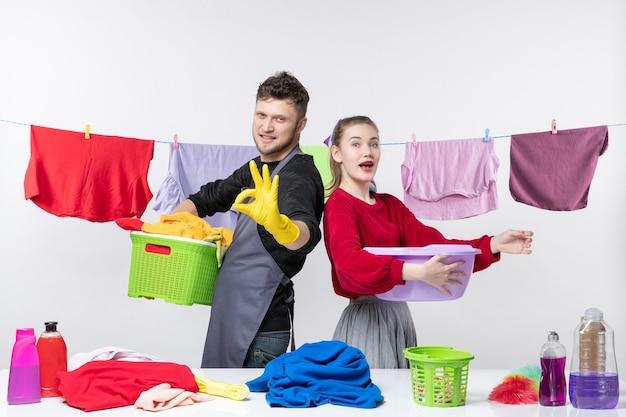 Vista frontal do jovem casal feliz fazendo sinal de ok, esposa segurando a banheira na parede branca