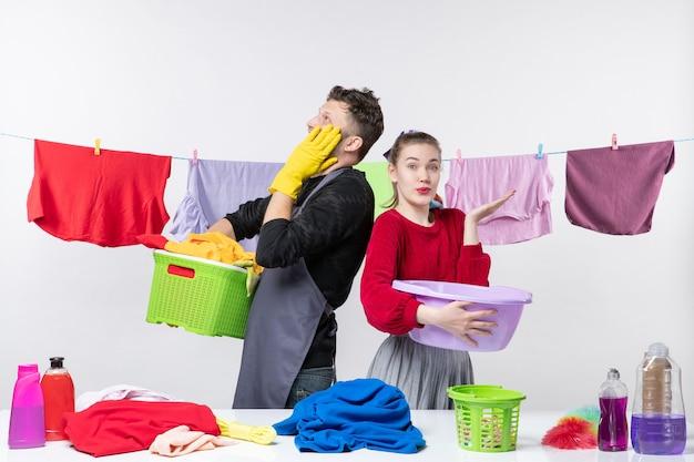 Vista frontal do jovem casal preparando a lavagem de roupas na parede branca