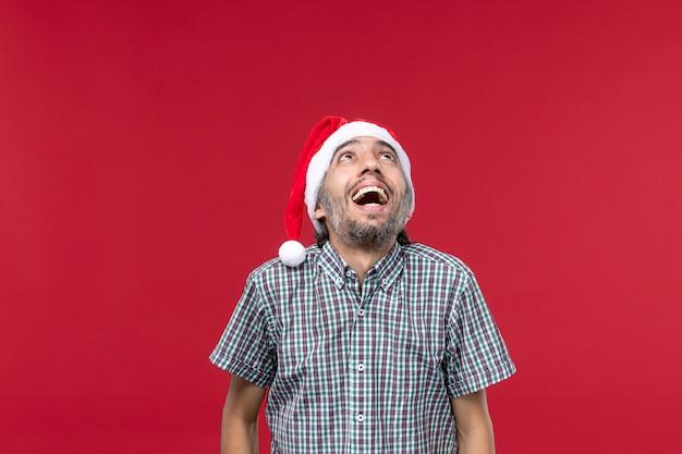 Vista frontal do jovem com expressão animada na parede vermelha feriado de ano novo vermelho