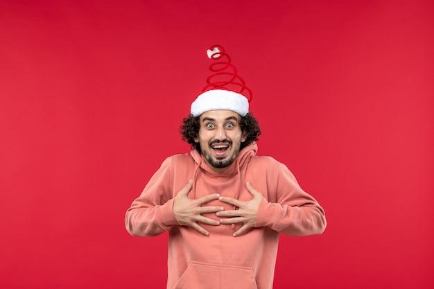 Vista frontal do jovem com expressão animada na parede vermelha