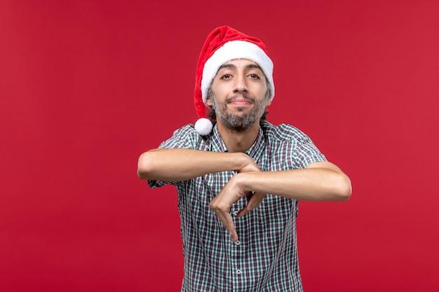 Vista frontal do jovem com expressão calma na parede vermelha, feriado de ano novo vermelho