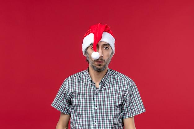 Vista frontal do jovem com tampa de ano novo na parede vermelha feriado de ano novo vermelho