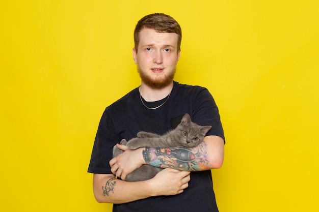 Vista frontal do jovem de camisa azul, segurando o gatinho cinzento bonito