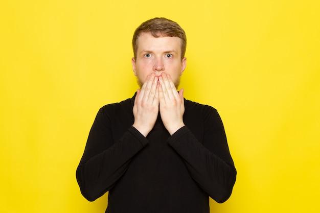 Vista frontal do jovem de camisa preta, posando com expressão chocada